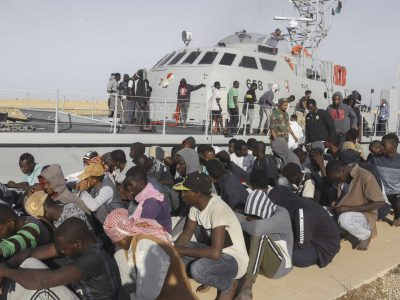 """FILE - In this Oct. 1, 2019 file photo, rescued migrants are seated next to a coast guard boat in the city of Khoms, around 120 kilometers (75 miles) east of Tripoli, Libya. The U.N. refugee agency plans to cut the number of migrants staying at an overcrowded transit center in Libya's capital, a spokesman said Saturday, Nov. 30.  Libya is a major waypoint for migrants fleeing war and poverty in Africa and the Middle East to Europe. """"The situation is very difficult, and we do not have the resources"""" because the center in Tripoli is at about twice its capacity, with some 1,200 migrants, Charlie Yaxley, a UNHCR spokesman, told The Associated Press.  (AP Photo/Hazem Ahmed, File)"""